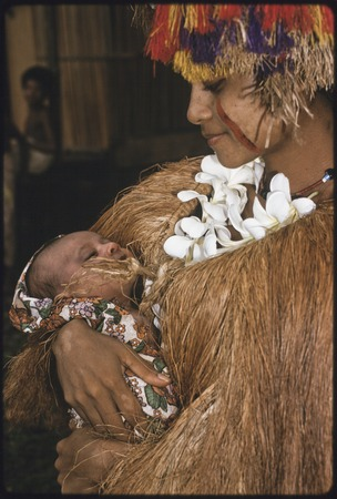 New mother, holding newborn, wears long fiber shawl, flower garland, and skirt valuable on head, red betel nut paste on face