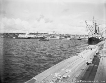 General view of San Diego harbor showing ships, boats, and lumber stacked on dock