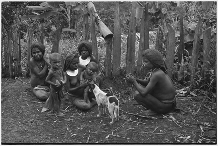 Women and children eat while dog watches