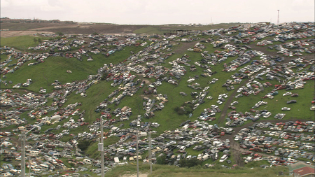 Osmosis and Excess: film still depicting Tijuana hillside covered in junk cars