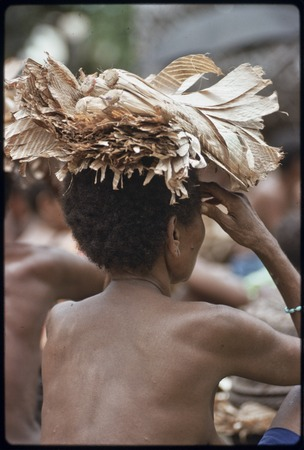 Mortuary ceremony: woman carries banana leaf bundle on her head