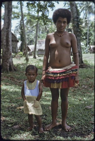 Adolescent girl wearing short fiber skirt stands with young girl in cloth dress, both wear red shell necklaces