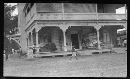 Verandah of royal palace, Tongatapu, with large piles of tapa and mats for ceremonial presentation.