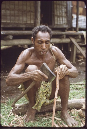 Canoe-building: Gisigesi uses axe to smooth a piece of wood for outrigger frame,  he smokes