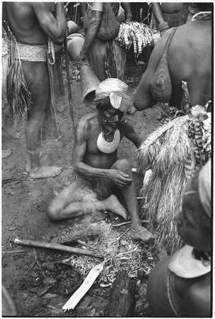 Pig festival, pig sacrifice, Tsembaga: older man sits by fire, surrounded by decorated men