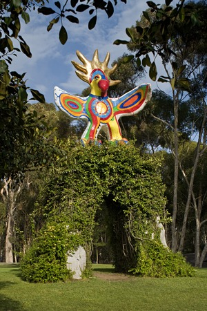 Sun God: front view with sculpture supported by vine-covered, concrete arch