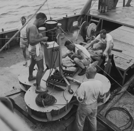 Willard N. Bascom, at left, readying instruments raft onboard R/V Spencer F. Baird. Bikini area. Capricorn Expedition, 1952