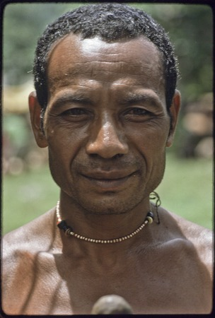Man wearing a shell bead necklace
