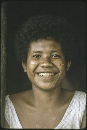 Smiling young woman with dashes of betel nut paste on her cheeks