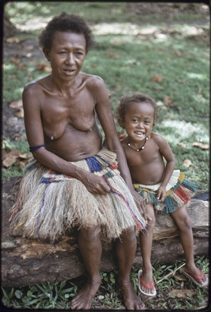 Mogiovyeka's wife and daughter, Imala, wearing fiber skirts, girl wears shell necklace