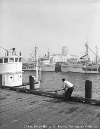 Man securing boat to pier, docked tuna boats in background