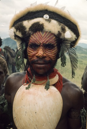 Man with elaborately painted face and wig with marsupial fur, wearing a specially fine baler shell for a ceremony