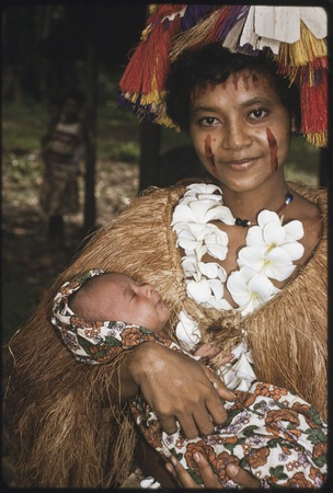 New mother, holding newborn, wears long fiber shawl, flower garland, and skirt valuable on head, and betel nut paste on face
