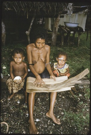 Woman folds strips of dried pandanus leaves (to be woven later), two children at her side