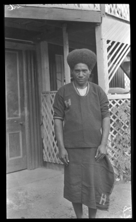 Ahuia, one of Lambert's Motu assistants, wearing uniform with H, standing for Hookworm.