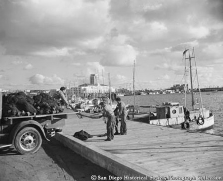 Men on Embarcadero unloading fishing nets from truck