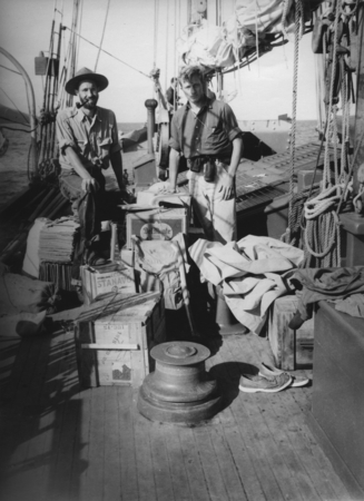 [Two men standing surrounded by supplies on deck of R/V E.W. Scripps]