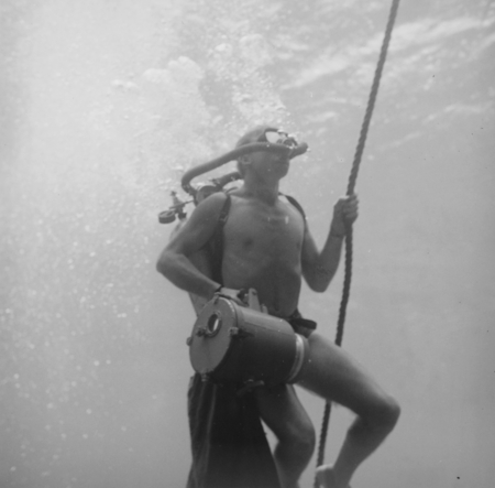 Phillip E. Jackson, diver and laboratory technician during the Capricorn Expedition (1952-1953), showed here carrying an u...