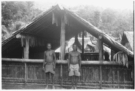 Two men in front of house.