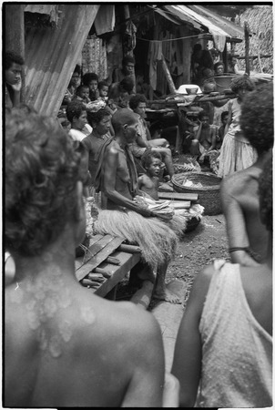 Mortuary ceremony: woman (center) holds banana leaf bundles for ritual exchange, large basket (r)