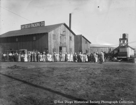 Distant view of employees gathered outside San Diego Packing Company cannery