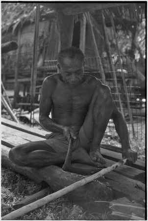 Canoe-building: man, Tovalugwa, smoothes thin pole, using an axe with traditional handle