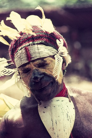 Villager, perspiring and fatigued, wears feathered looped headdress with trade-bead headband, face paint and baler shell v...