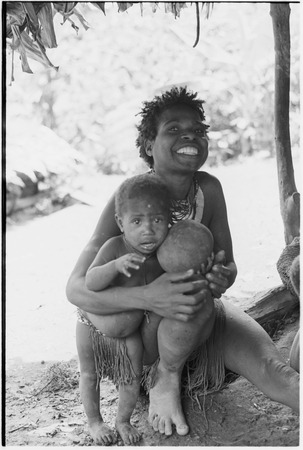 Bomagai: smiling woman with a young child who holds ball made from pig's bladder