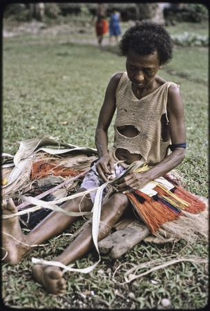 Weaving: woman makes colorful skirt from dyed banana fibers, tying them to cord held around her waist and foot