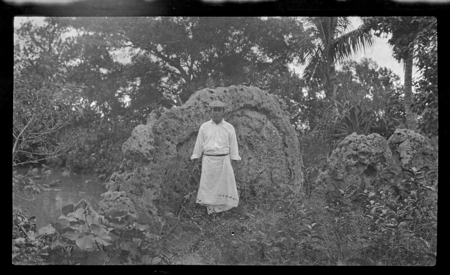 Portrait of man, standing in front of possible shrine.