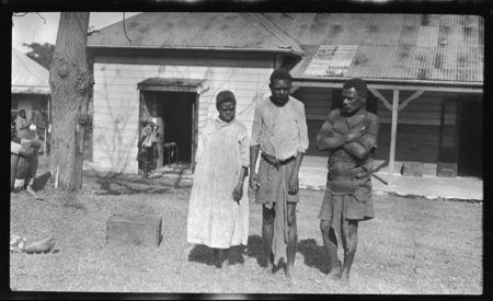 Two men and a woman in torn clothes, outside a building  | Library