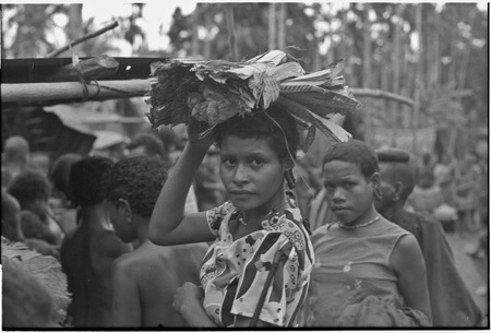 Mortuary ceremony, Omarakana: woman in Western-style blouse, carries banana leaf bundles on her head at ritual exchange