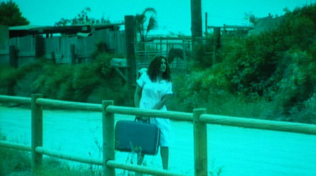 Border stories working title from one side to another: film still of woman carrying suitcase down a road