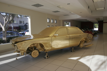 The Jewel / In God We Trust: junk car covered in gold leaf in luxury car dealer showroom