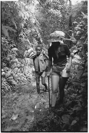 A European woman walking up stream with Kwaio boy.