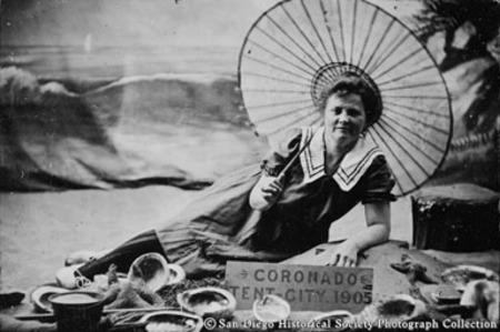 Woman in bathing suit posing with parasol, seashore props, and sign reading, ntserCoronado, Tent City, 1905""
