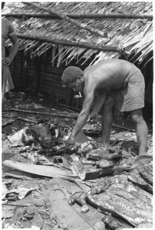 Man with pig head on pile; the head is sacred.