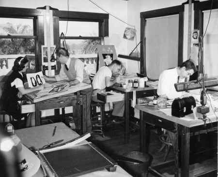Left to right: unidentified woman, illustrator Lindsay L. Field, Sam Hinton, and unidentified man at work in the Training ...