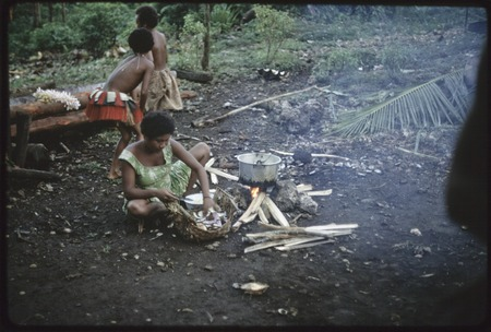 Food preparation: Kitemwalusa peels yams for cooking, girl in red skirt behind her
