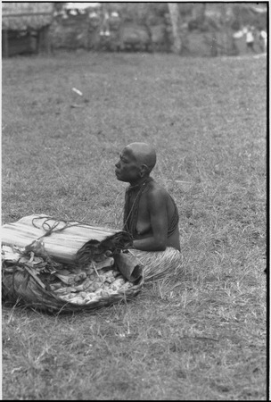 Mortuary ceremony, Omarakana: mourning woman, face and body covered with ash, with basket of banana leaf bundles and mats
