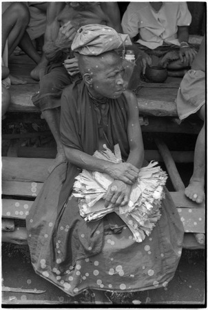 Mortuary ceremony: mourning woman with banana leaf bundles, she wears a cloth skirt