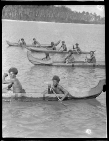 Several men rowing canoes.