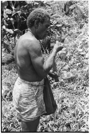 Larikeni talks to his ancestors with a betel nut, areca, and then eats it.