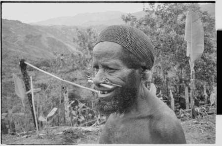 Older man with pierced nose, wears a cap netted from plant fibers