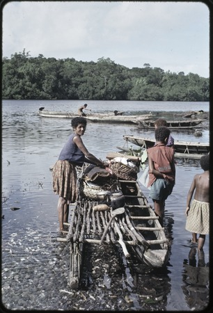 Canoes: women load items onto canoe used for coastal transport
