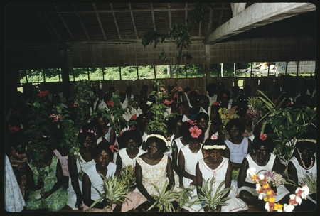 Group of women in a building: seated, holding plants, and flowers in hair
