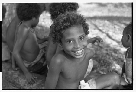 Smiling boy looks at camera, other children in background