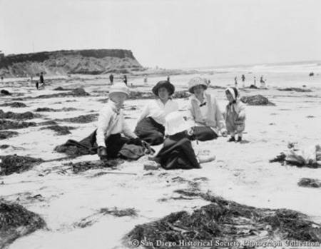Women sitting with children on beach covered with kelp