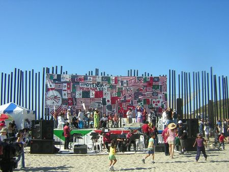 One Flew Over the Void (Bala perdida): border fence decorated with banners behind performance stage