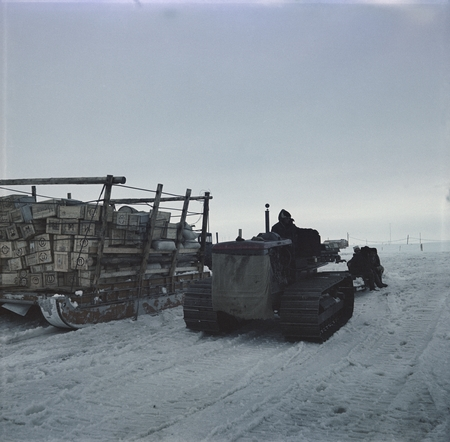 Tractor sledge train unloading supplies from research ship Ob
